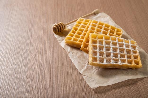 Deliciosos waffles belgas com mel. produtos de confeitaria. comida