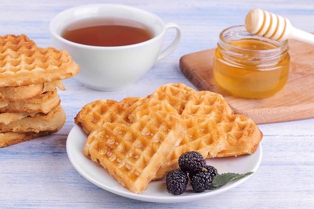 Deliciosos waffles belgas doces em forma de coração com mel e chá em uma mesa de madeira azul. café da manhã.
