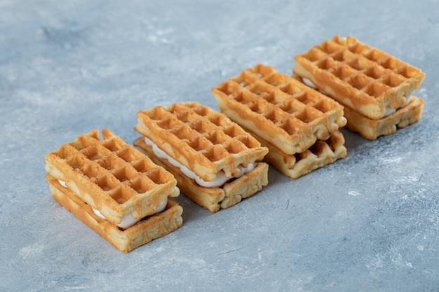 Deliciosos waffles colocados em superfície de mármore.