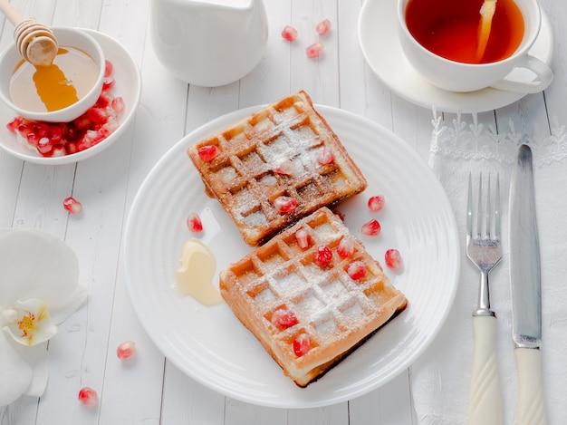 Deliciosos waffles de dar água na boca com sementes de mel e romã em um prato branco