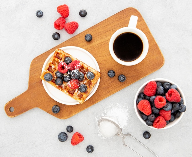Deliciosos waffles doces e café na tábua de madeira