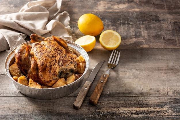 Delivery de frango assado com batatas na mesa de madeira