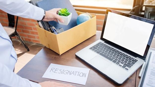 Demissão de empresário arrumando todos os seus pertences pessoais e arquivos em uma caixa de papelão marrom