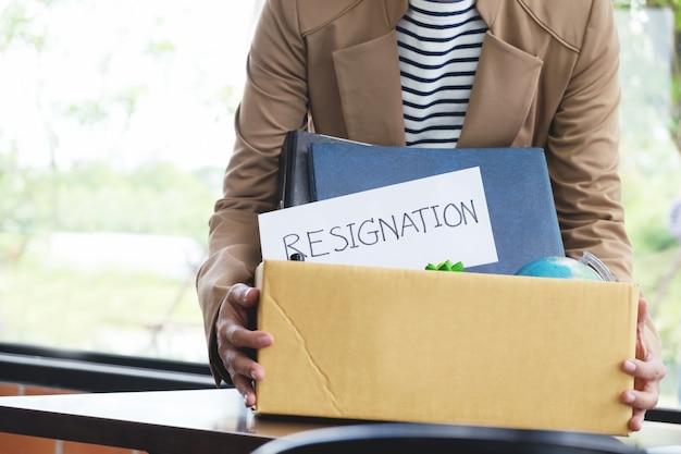 Demissão empresária arrumando todos os seus pertences pessoais e arquivos em uma caixa de papelão marrom.