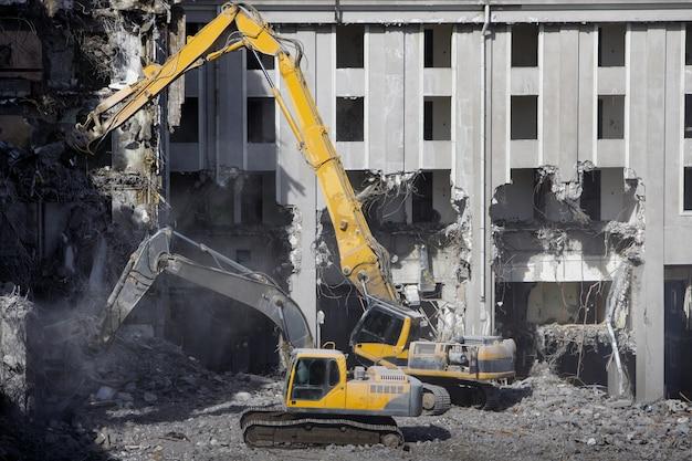 Demolição para novas construções, usando uma escavadeira-destruidora hidráulica especial dois