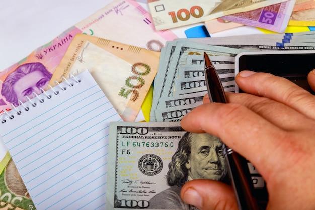 Denominações da hryvnia ucraniana das contas nas notas sob um fragmento da nota de dólar dos eua.
