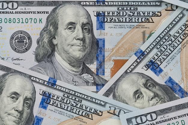 Denominações de cem dólares americanos. espalhe na mesa. fechar-se. não visibilidade total das notas.