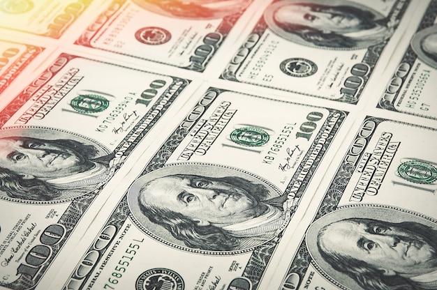 Denominações de cem dólares são organizadas em uma fileira. brilha no canto. ver em ângulo.