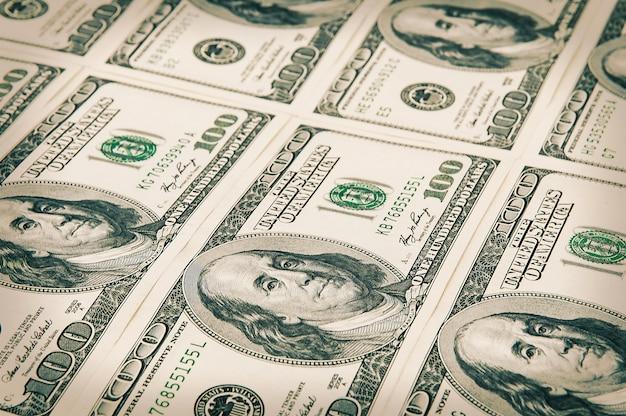 Denominações de cem dólares são organizadas em uma fileira. processamento sob a antiguidade. ver em ângulo.