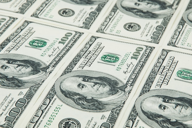 Denominações de cem dólares são organizadas em uma fileira. ver em ângulo. isolado.