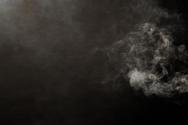 Densas nuvens fofas de fumaça branca e nevoeiro em fundo preto, nuvens de fumaça abstratas, movimento desfocado fora de foco. golpes de fumaça da máquina de gelo seco voam e tremulam no ar, efeito de textura