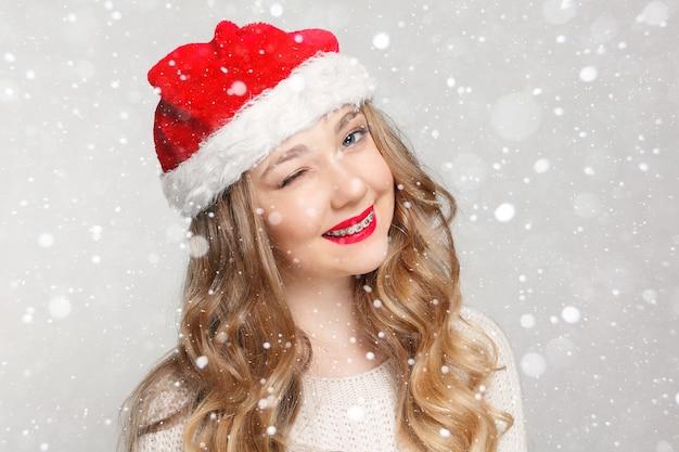 Dental, natal, natal, inverno, conceito de felicidade - mulher sorridente com chapéu de ajudante de papai noel, bela modelo feminino usar chapéu de papai noel. menina com aparelho dentário