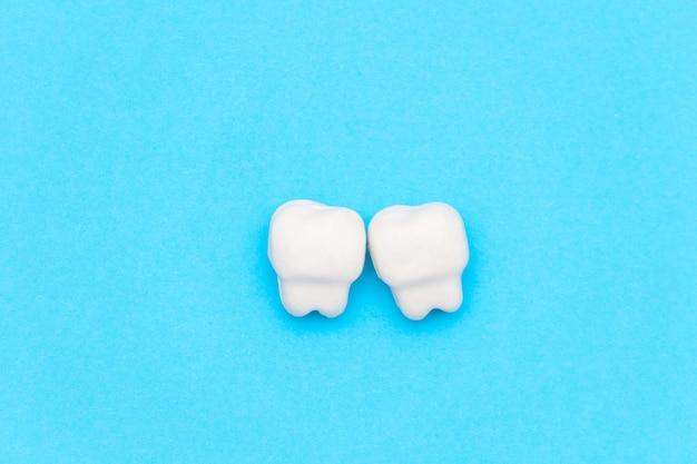 Dente branco, espaço para texto em cor de fundo azul. conceito de dentes saudáveis.