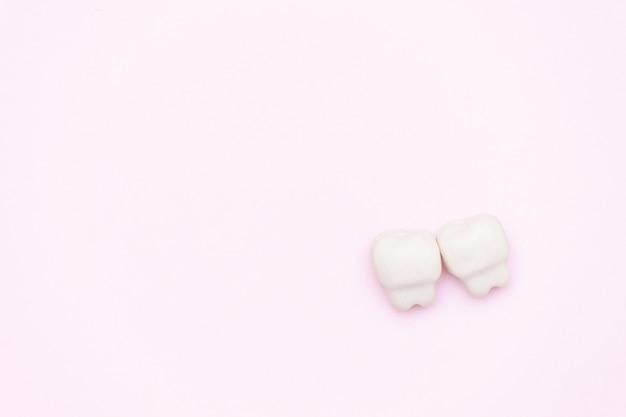 Dente branco, espaço para texto em fundo cor de rosa. conceito de dentes saudáveis.