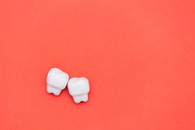 Dente branco, espaço para texto em fundo de cor vermelha. conceito de dentes saudáveis.
