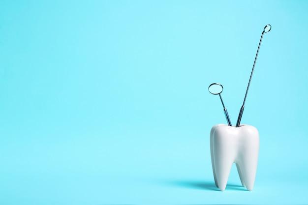Dente branco saudável e espelhos dentista sobre fundo azul claro.