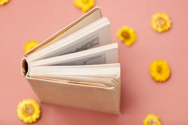 Dente-de-leão amarelo e livro rosa