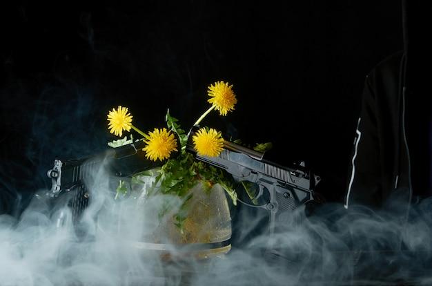 Dente de leão com raízes e folhas em um bule de vidro e com duas pistolas