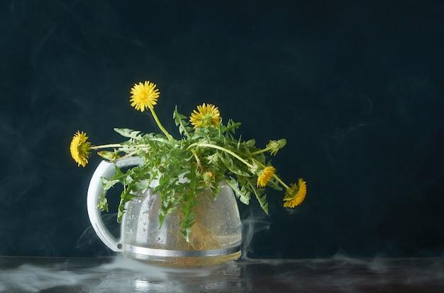 Dente de leão com raízes e folhas em um bule de vidro