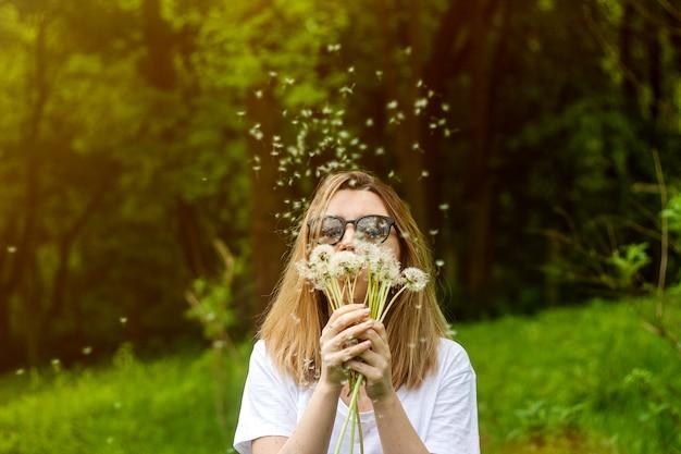 Dente-de-leão de sopro da jovem mulher no parque do verão.