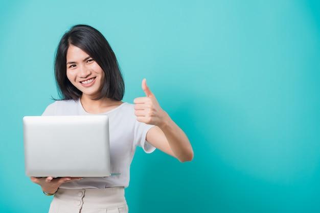 Dentes brancos de sorriso de mulher em pé para segurar o computador portátil e aparecer o polegar