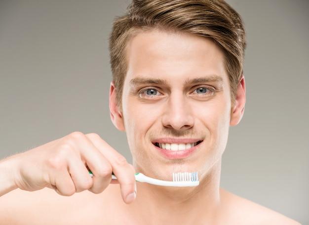Dentes consideráveis da limpeza do homem com a escova de dentes no banheiro.