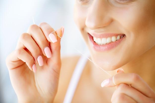Dentes de mulher jovem e bonita close-up com espaço de cópia no lado direito