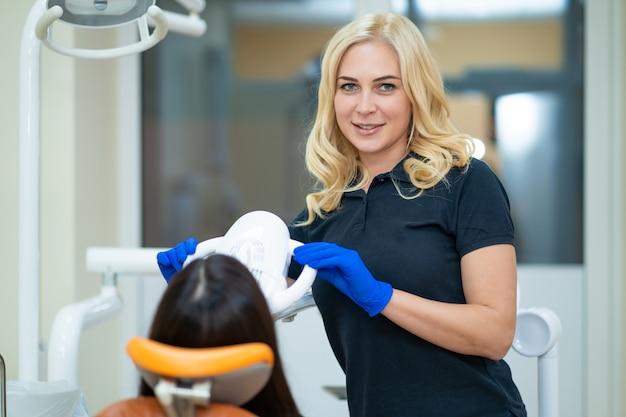 Dentes de publicidade modelo feminino lindo clareamento em uma clínica odontológica com equipamentos profissionais.