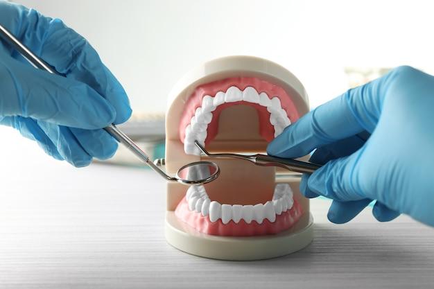 Dentes falsos brancos na mão do dentista, sobre fundo claro