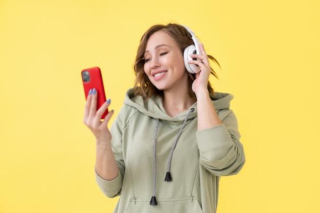 Dentes felizes, sorriso, mulher, ouvir música, fones de ouvido segurando o smartphone na mão, olhando a tela mulher caucasiana, desfrutar de podcast ou audiolivros vestida com capuz grande fundo amarelo close-up retrato