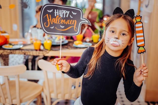 Dentes gengivais. uma linda gata engraçada de cabelos escuros participando da festa de halloween com gengivas na boca