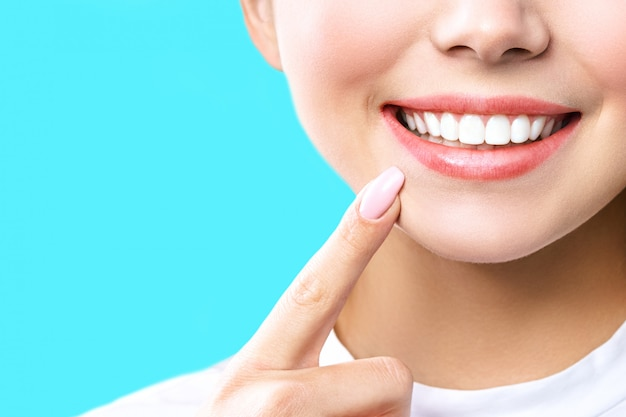 Dentes saudáveis perfeitos sorriem de uma jovem mulher
