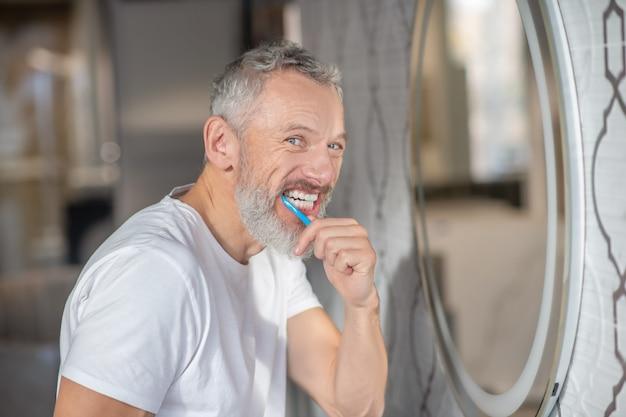 Dentes saudáveis. um homem escovando os dentes com uma nova pasta de dente