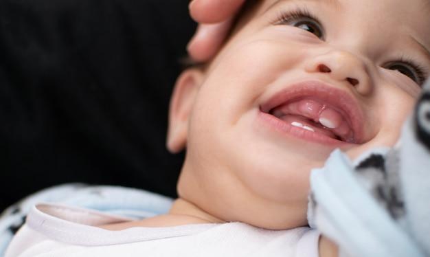 Dentição bebê tem um grande sorriso mostra a goma e dente que vem