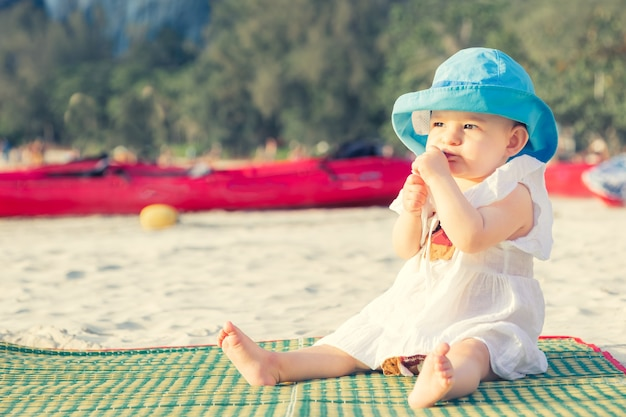 Dentição em 8 meses menina sentada na praia mastigando um mordedor na esteira de bambu