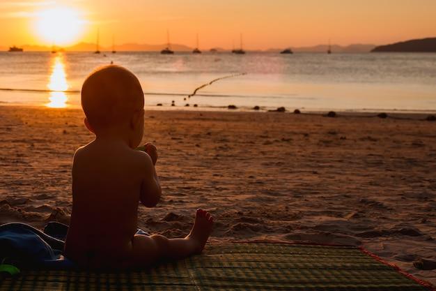Dentição em nove meses menina sentada em uma praia tropical mastigando um mordedor pôr do sol no mar