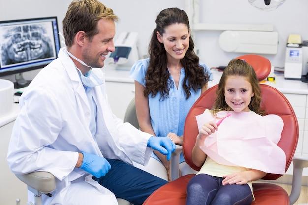 Dentista ajudando paciente jovem a escovar os dentes