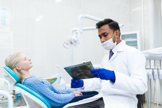 Dentista asiático masculino no consultório odontológico, conversando com uma paciente do sexo feminino e se preparando para o tratamento. equipamento médico moderno