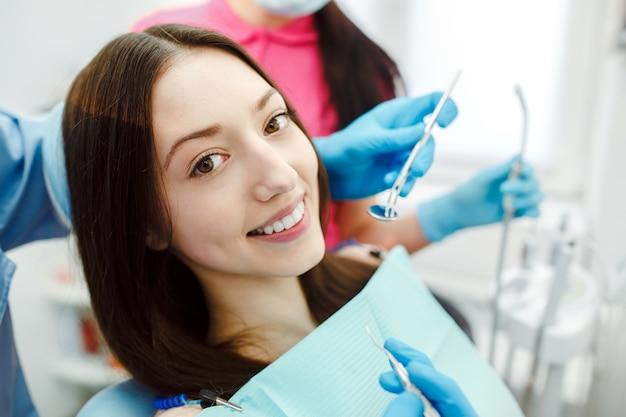 Dentista assistente e o paciente na clínica.