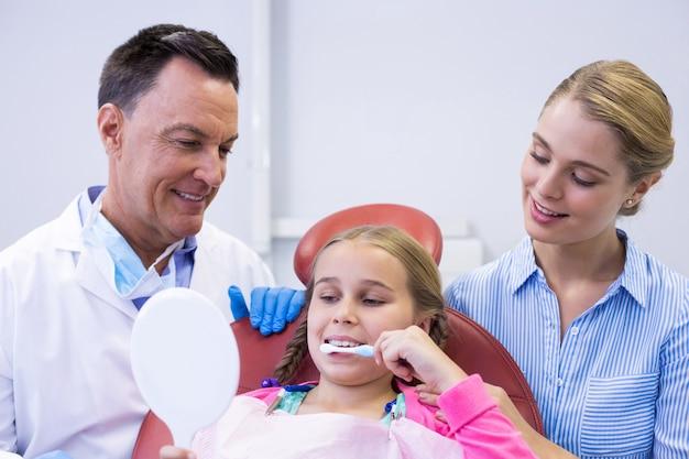 Dentista auxiliando paciente jovem enquanto escova os dentes