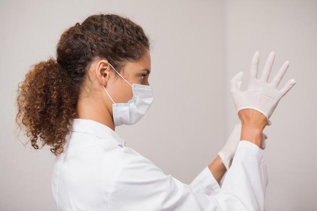 Dentista colocando luvas cirúrgicas