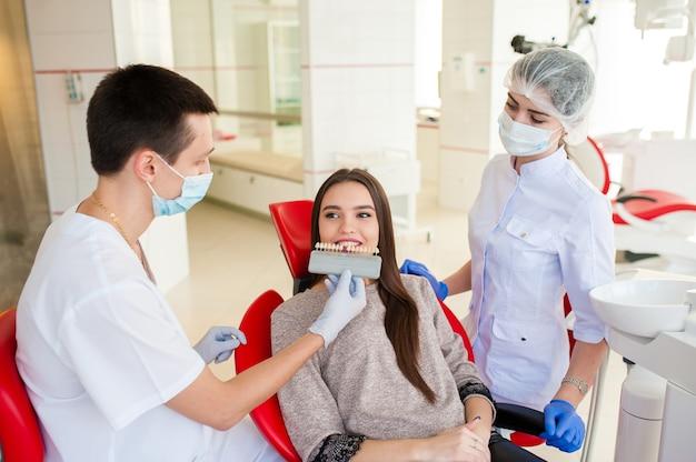Dentista com assistente, escolha a cor dos dentes para uma bela mulher