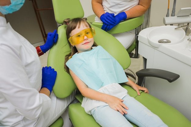 Dentista com garota na cadeira