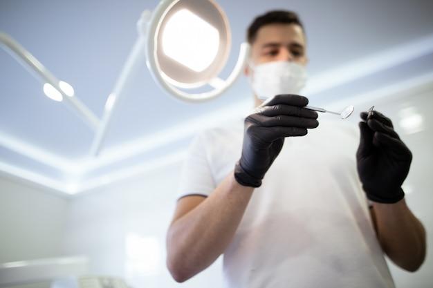 Dentista com instrumentos iniciando um procedimento