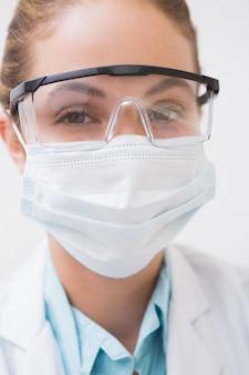 Dentista com máscara cirúrgica e óculos de proteção na clínica odontológica