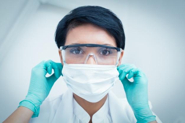 Dentista com máscara cirúrgica e óculos de segurança