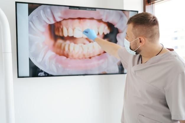 Dentista com máscara médica apontando para os dentes do paciente em uma tela grande explicando as fases do tratamento