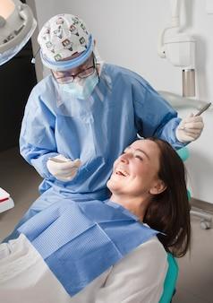 Dentista com paciente na cadeira odontológica, eles riem juntos,