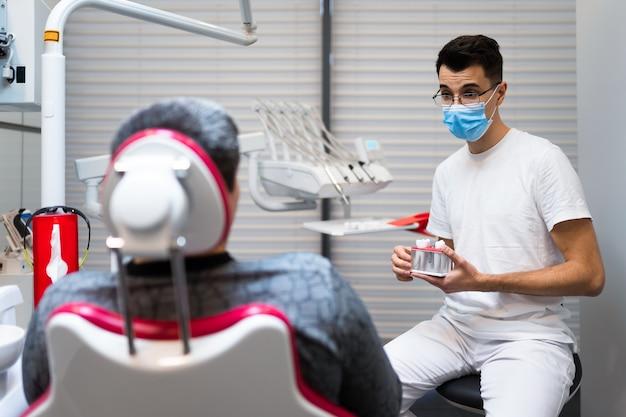 Dentista conversa com paciente sobre próteses.