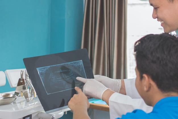 Dentista, conversando com seu paciente, explicando a radiografia de raio-x